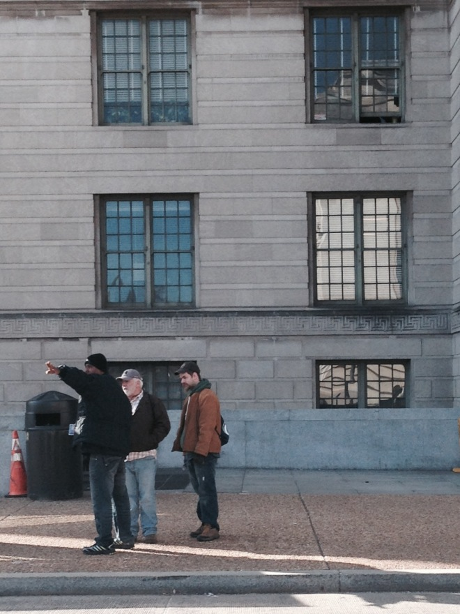 These three men were standing in front of the U.S. Department of Agriculture. The two men on the right were asking the third man for directions. He was giving them directions gesticulating a bit wildly.